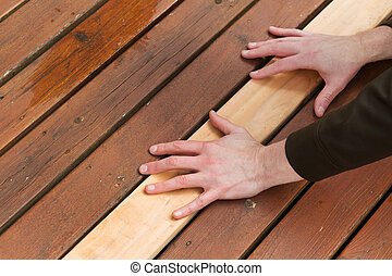 Replacing Cedars Boards on Deck - Horizontal photo of male...