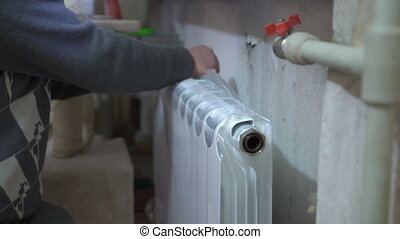 Replacing of old hot water radiator with new. Closeup of...
