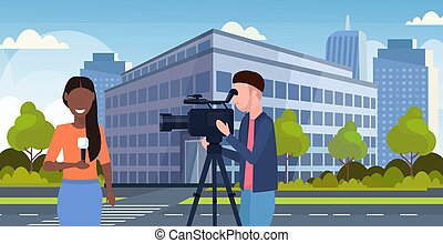 reporter man with woman journalist presenting live news operator using video camera on tripod recording correspondent with microphone movie making concept cityscape background portrait horizontal