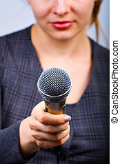 Reporter with microphone taking interview or opinion poll