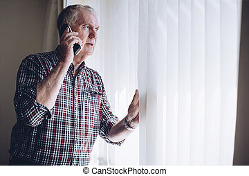 Reporting a Crime - Senior man talking on the phone whilst...