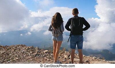 reposer, randonneurs, homme, bord, couple, apprécier, voyage, paysage., debout, vue, endroits, dos, chariot, sacs dos, femme, beau, montagne, ensemble., explorer, nouveau, coup, pendant, arrière-plan., activement