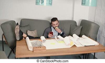 reposer, smartphone, pomme mangeant, séance, travail évitant, jeune, pieds, sien, usages, sofa, mettre, table, homme