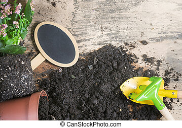 Repotting activity with a blooming plant, a flower pot overturned, soil, gardening tools, and a blank black banner, on a vintage wooden table.