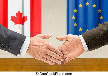 Representatives of Canada and the EU shake hands