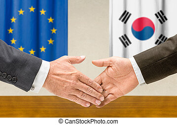 Representatives of the EU and South Korea shake hands
