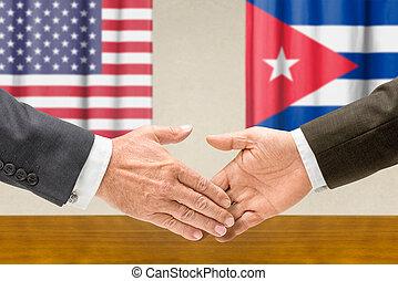 Representatives of the USA and Cuba shake hands