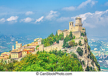 Republic San Marino Prima Torre Guaita first fortress tower with brick walls on Mount Titano stone rock with green trees, aerial top panoramic view of landscape valley and hills of suburban district