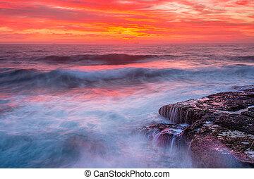Res skies over ocean as waves surge over rocks