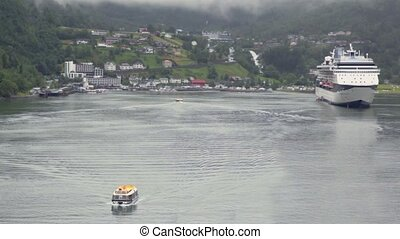 Rescue boat float on fiord to huge liner near coastal...