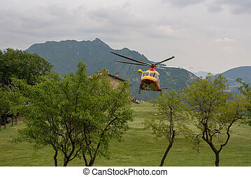 rescue helicopter landing on a lawn for the recovery of an injured person