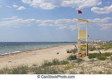 Rescue tower with a red flag on the beach of the resort village Vitino in the Saksky district of the Crimea
