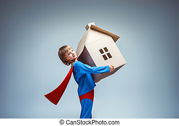 Rescuer - Boy in a superman costume with cardboard house