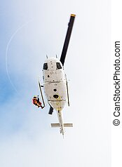 Rescuer descending from helicopter - Rescuer descending from...