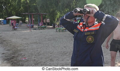 Rescuer with binoculars on the beach
