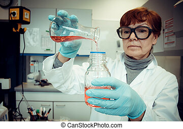 Research Assistant works with red liquid in laboratory