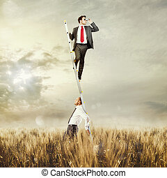 Research with support - Man holds up the ladder to a man...