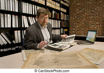 Researcher in archive, searching through maps and...