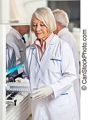 Researcher Loading Samples In Analyzer