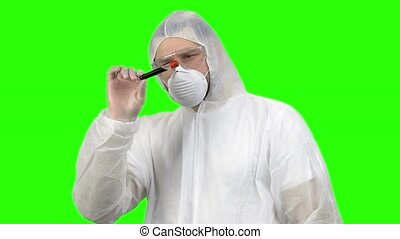 Researcher or scientist in protective clothing looking at blood test tube. Green screen background for keying.