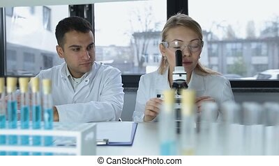 Researchers microscoping in biochemistry lab