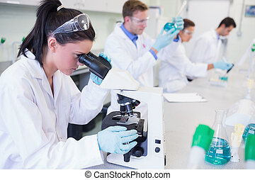 Researchers working on experiments in lab - Side view of...