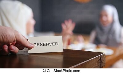 Reserved sign on the table. Two muslim woman sitting on the background and talking. A person removes the sign from the table. Mid shot