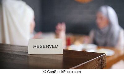 Reserved sign on the table. Two muslim woman sitting on the background and talking. Mid shot