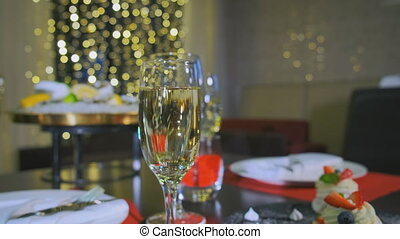 A reserved table in the restaurant, a close-up glass of champagne. Camera slide to the right