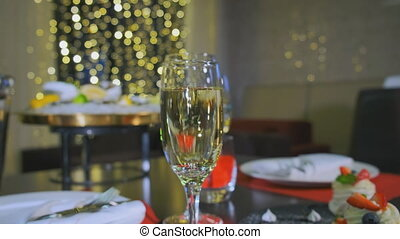 A reserved table in the restaurant, a close-up glass of champagne. Camera slide to the left
