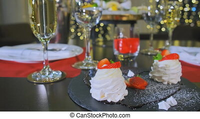 A reserved table in the restaurant in the evening, a close-up of a delicious dessert. Camera goes to the left