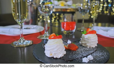A reserved table in the restaurant in the evening, a close-up of a delicious dessert. Camera goes to the right