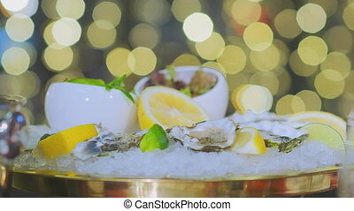 A reserved table in the restaurant in the evening, a close-up of oysters in the ice. Camera slowly slide to the left