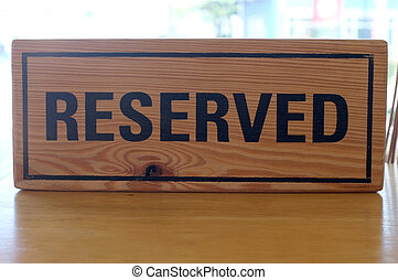 Reserved wooden sign on table