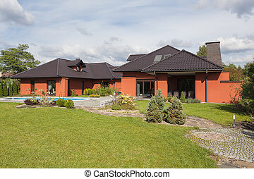 Residence with garden - A black and coppery residence with a...