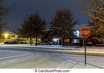Residential area and parking lot snowy winter night street lit by in the snowy road