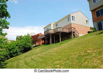 Residential back yard with house sitting on a slope in the summer time.