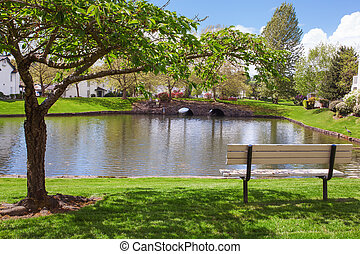 Residential complex backyard garden with pond, trees and sitting