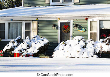 Residential home decorated for Christmas covered in snow after a storm