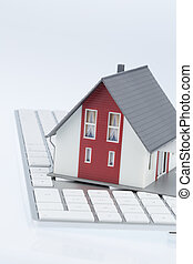 residential house on keyboard, symbolic picture for buying a...