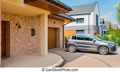 Residential house with silver suv car parked on driveway in front