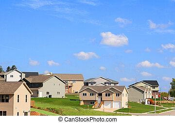 A modern neighborhood on a hill with a bright blue sky