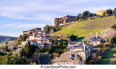 Residential neighborhood with multilevel single family homes, built on a hilly area; water tank visible on top of the hill; Hayward, East San Francisco Bay Area, California