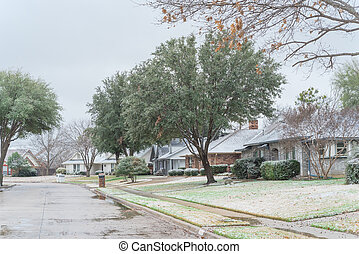 Residential street with bungalow houses under winter snow cover near Dallas