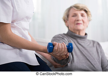 Resistance training with dumbbell - Senior woman during...