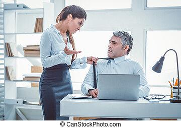 Resolute beautiful woman grabbing tie of her workmate