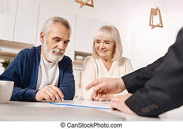 Resolute elderly couple signing agreement at home