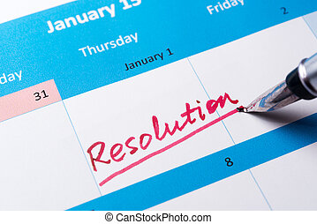 Resolution word written on the calendar with a pen