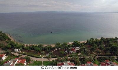 Resort area with cottages on the coast of vast blue sea,...