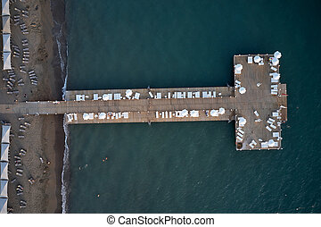 Resort coast with wooden pier in the sea, aerial view.